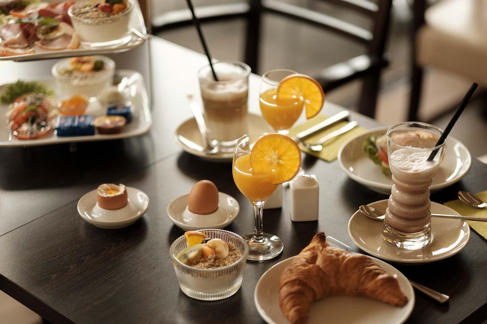 Lecker gedeckter Frühstückstisch mit Cappuccino, Latte Macciato, Orangensaft, Müsli mit frischen Früchten, Eiern, Wurstaufschnitt