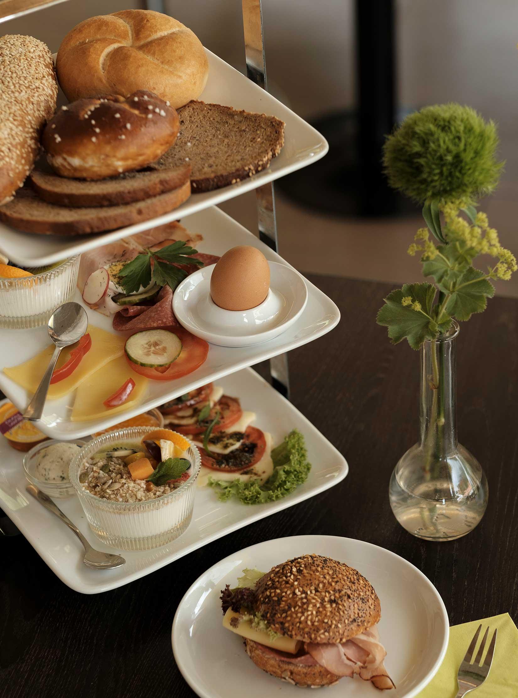 Etagere für ein reichhaltiges Frühstück mit Müsli, Tomaten, Mozzarella, Eier, Schinken, Salami, Semmeln, Laugenbrötchen, Brot