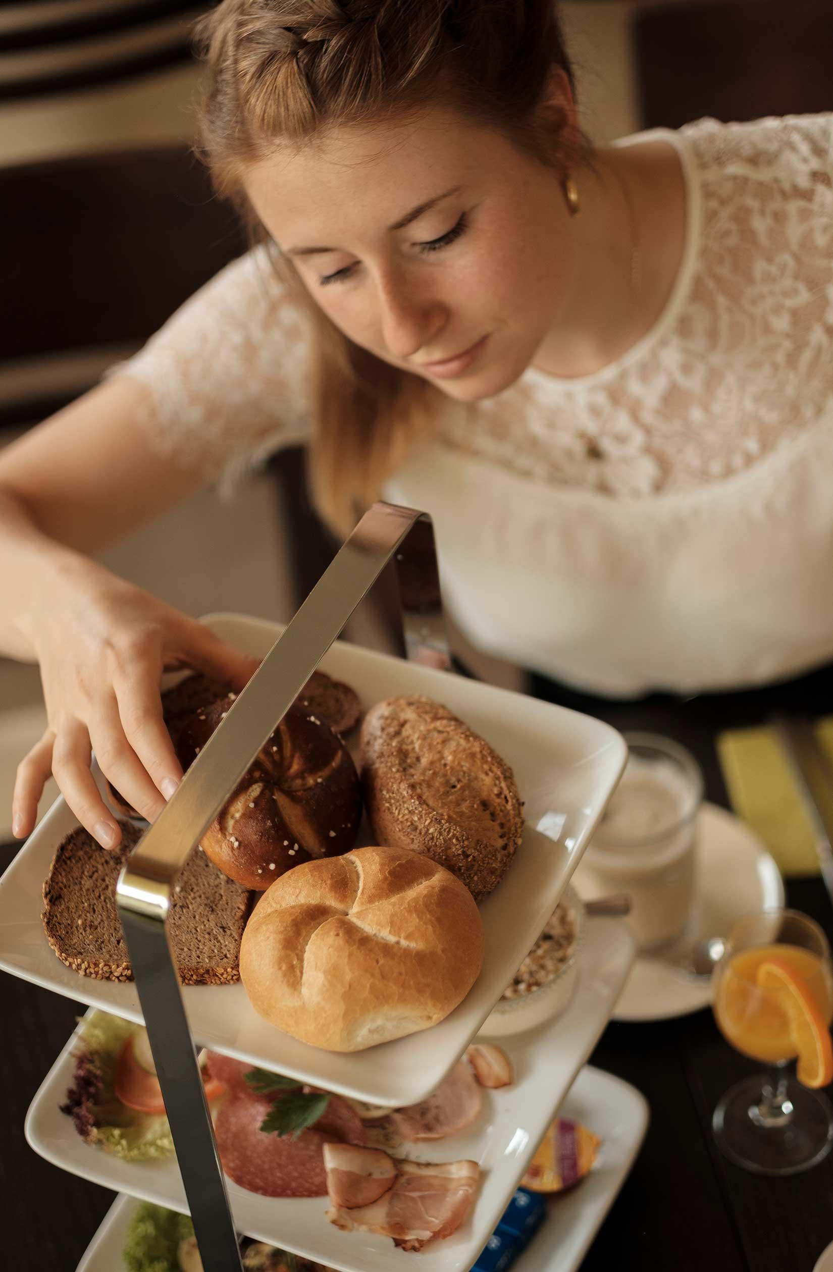 Frühstück mit frischem Gebäck wie Semmeln und Holzofenbrot, Cappuccino, Orangensaft, Salami, Schinken
