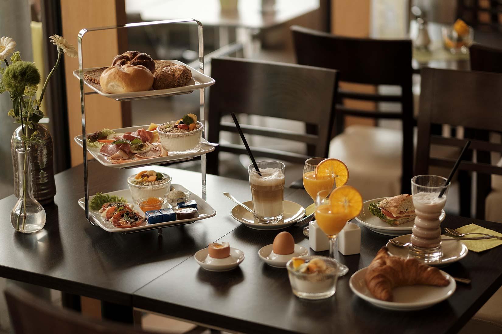 Reich gedeckter Frühstückstisch mit Orangensaft, Eiern, Croissants, Kaffee, Müsli, Wurst und Käse, frischen Früchten und vielen leckeren Spezialitäten