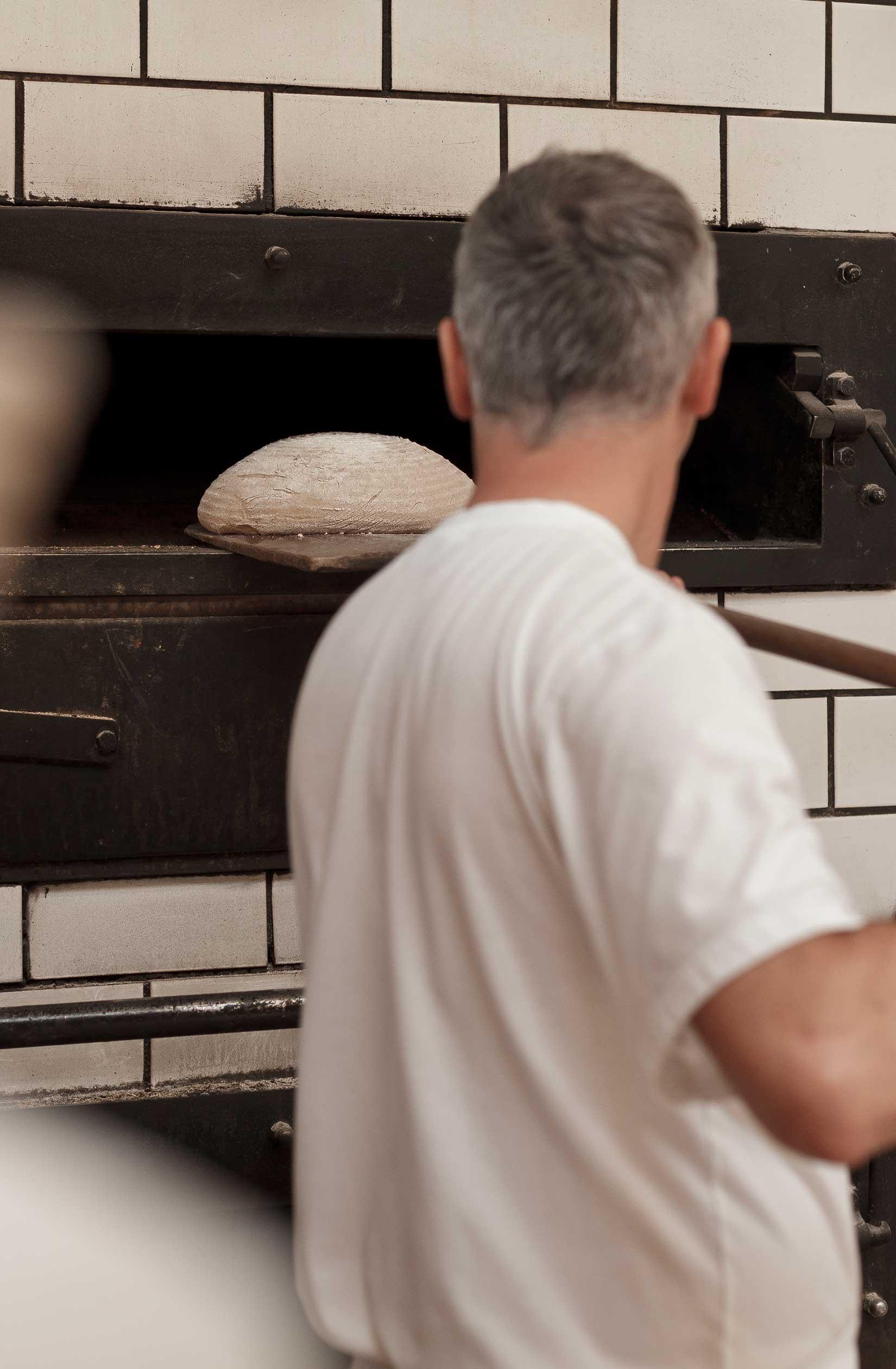 Thomas Schütz mit Holzschieber am Holzofen