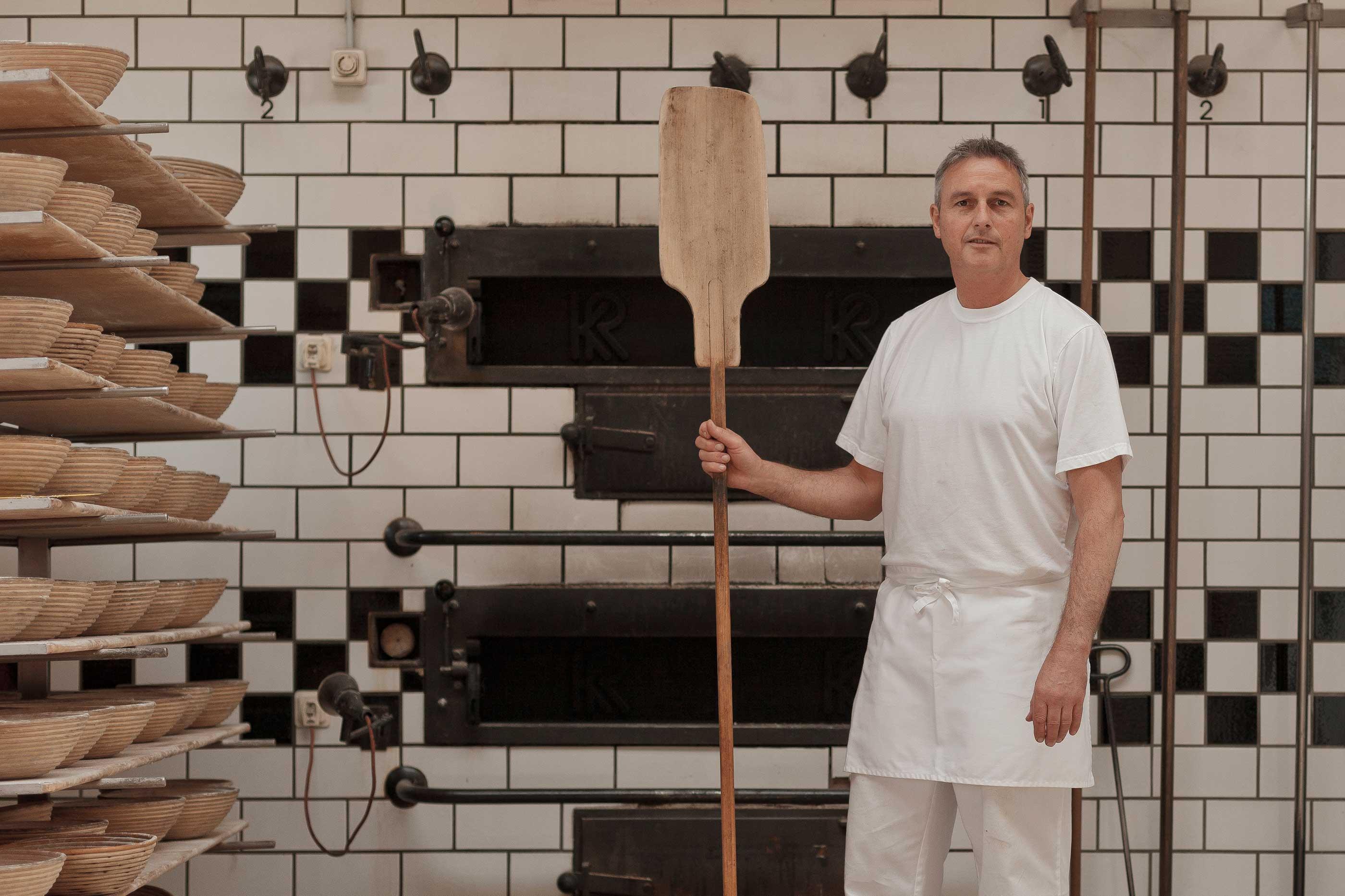 Bäckermeister Thomas Schütz aus Erkheim mit Brotschieber vor seinem Holzofen